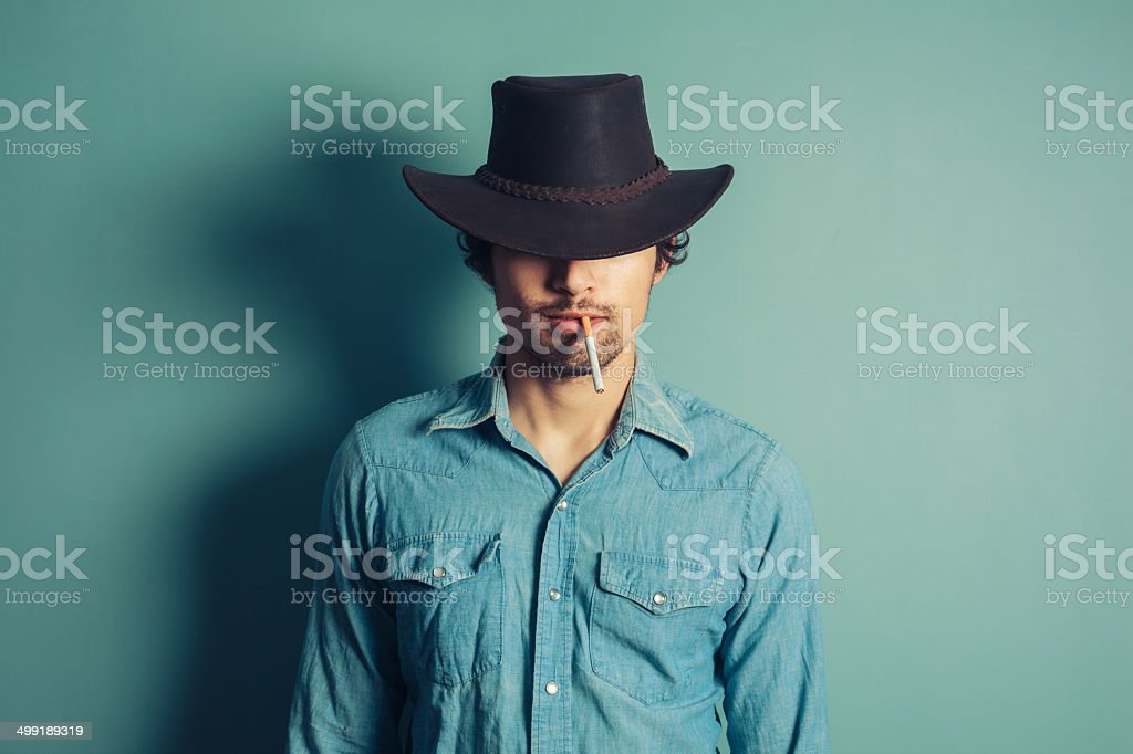 Young cowboy smoking cigarette stock photo