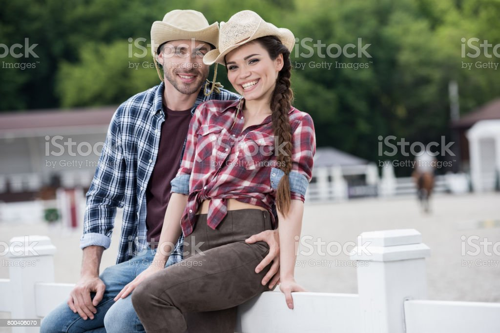 young cowboy style couple embracing and looking at camera while sitting on fence stock photo
