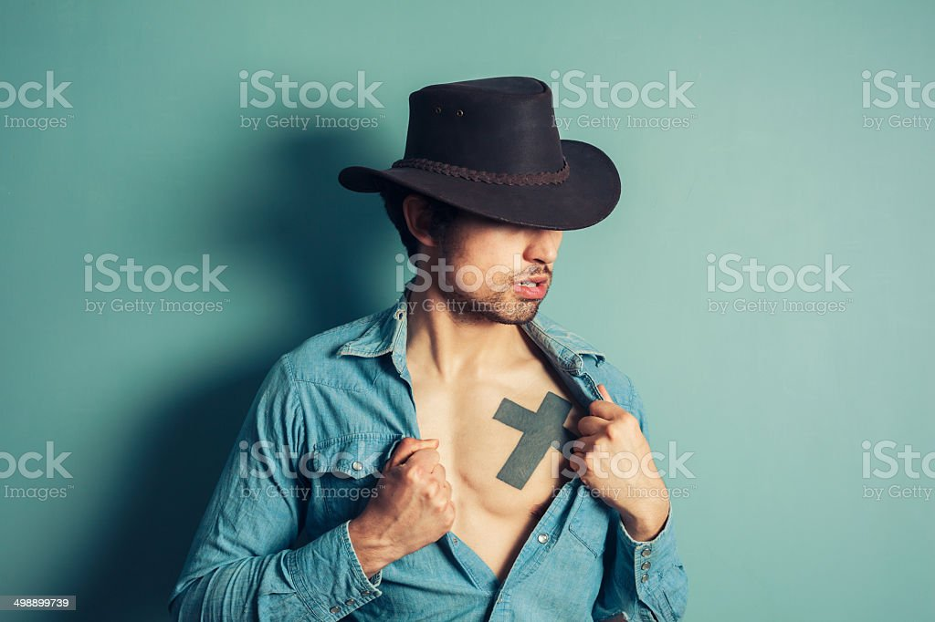 Young cowboy unbuttoning his shirt stock photo