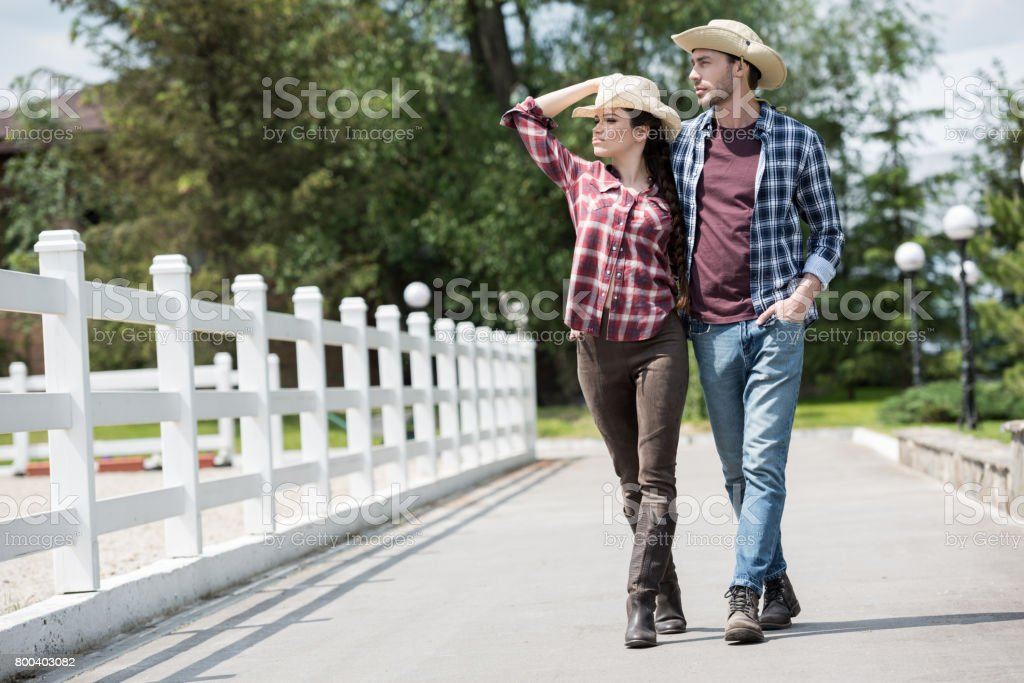 young cowboy with his girlfriend walking on pathway in park at daytime stock photo