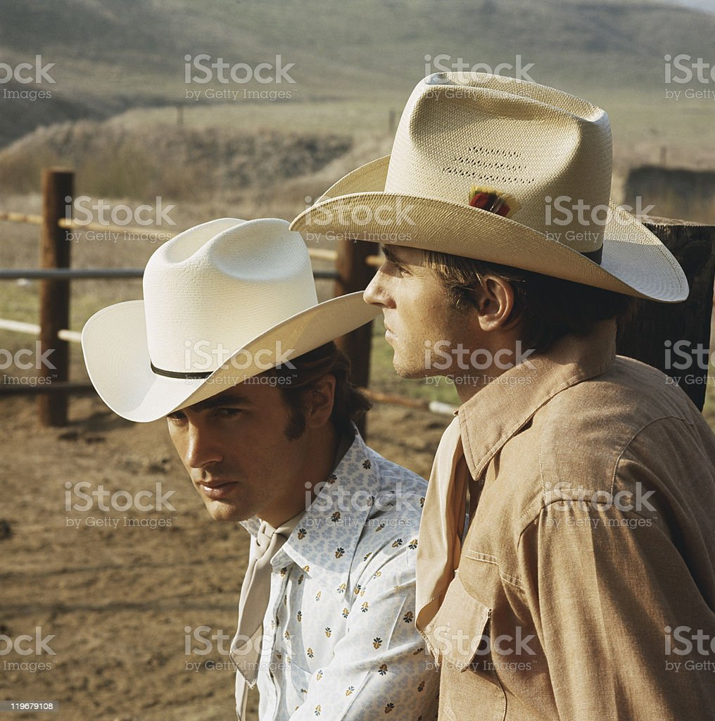 Young cowboys standing in ranch, close-up stock photo