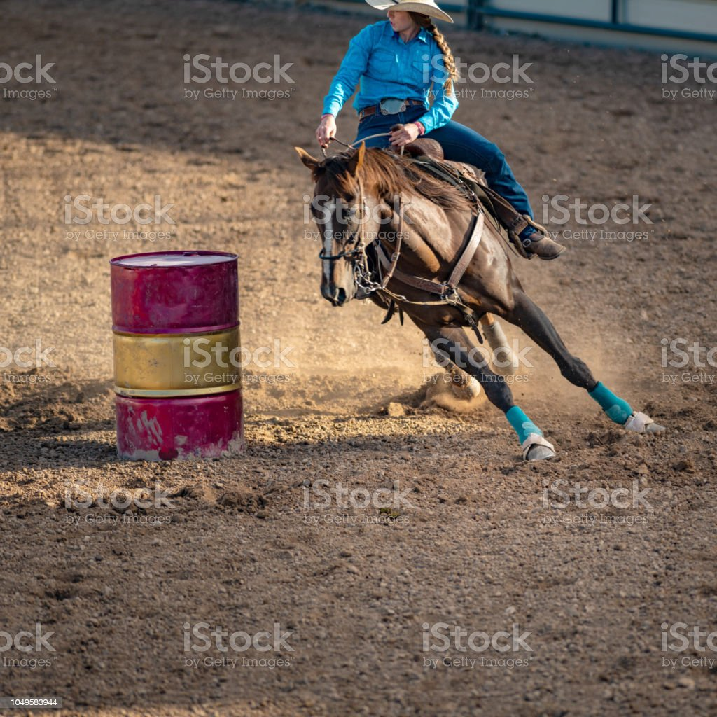 Young cowgirl barrel racing rodeo stock photo
