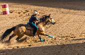 Young cowgirl barrel racing at a local rodeo arena