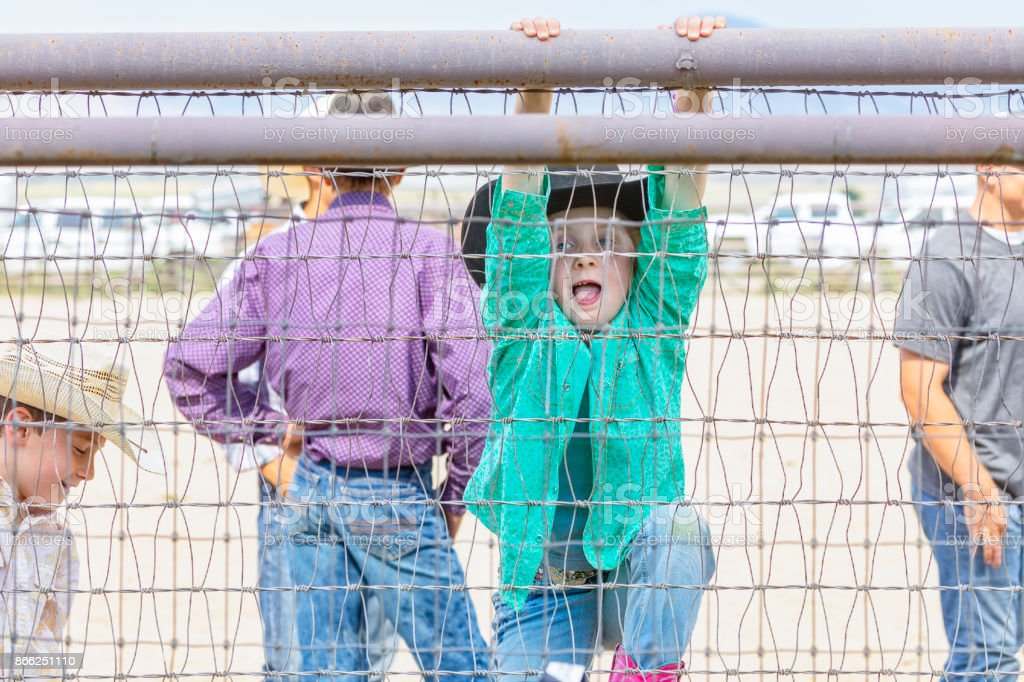 Young cowgirl begins climbing a fence at the rodeo stock photo