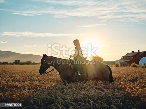 A young cowgirl with her horse on a ranch in Utah, USA.