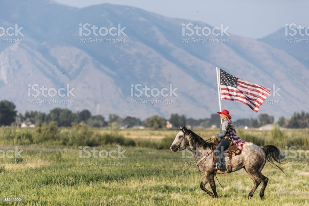 Young cowgirl riding her horse while proudly holding the American flag in a Utah field, with the Wasatch mountains visible in the background. stock photo