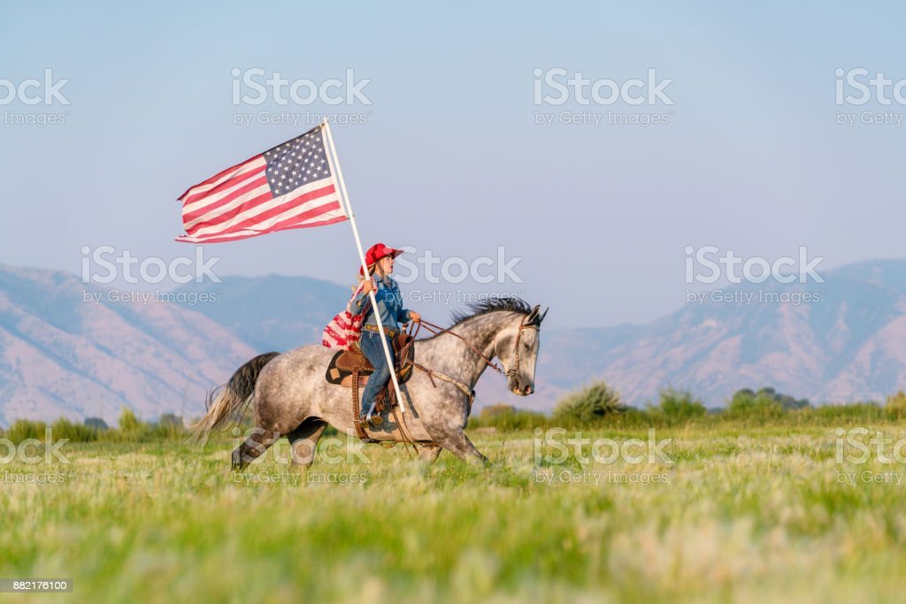 Young cowgirl wearing an American flag riding a horse stock photo