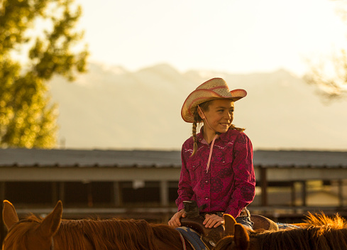 young cowgirl with hat riding her horse at ranch in Salt Lake City SLC Utah USA