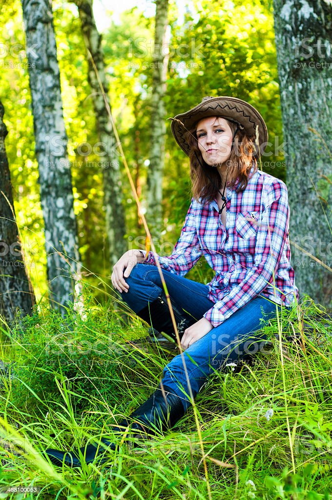 Young cowgirl woman siting in green forest in a grass royalty-free stock photo
