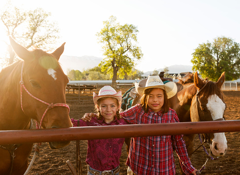 young cowgirls with hat and horses at ranch in Salt Lake City SLC Utah USA