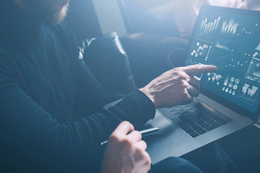 istock Young coworkers discussing business ideas at modern office.Bearded man poiting hand to laptop display.Woman sitting close him and holding pen on her hand. Horizontal, blurred, visual effect. 658555432