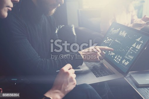 istock Young coworkers discussing business ideas at workplace.Bearded man poiting hand to laptop display.Woman sitting close him and holding pen on her hand. Horizontal, blurred, visual effect. 658556354