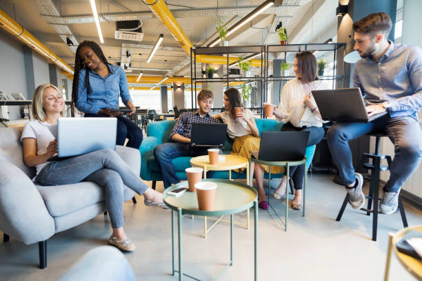Young coworkers in modern office Young people making strategy for startup business in modern co working space coworking stock pictures, royalty-free photos & images