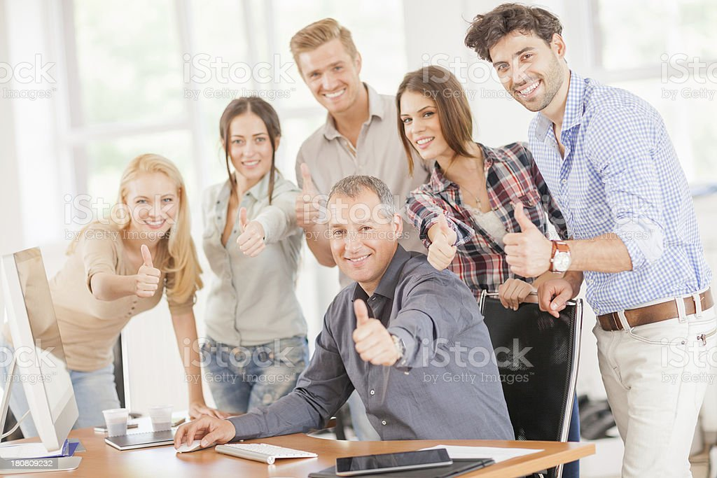 Young coworkers showing thumbs up royalty-free stock photo