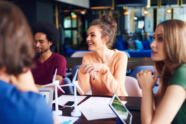 Young coworkers talking at conference table Young coworkers talking at conference table student life stock pictures, royalty-free photos & images