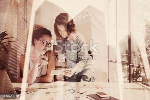 629421870 istock photo Young coworkers working at modern workplace in loft.Two girls 629422018
