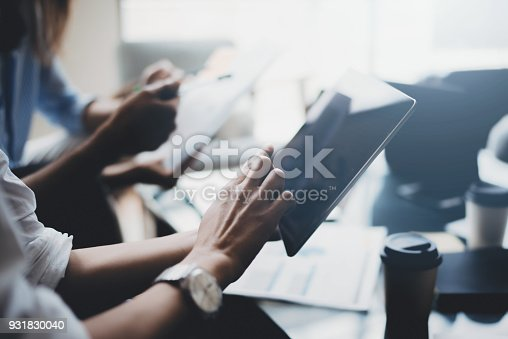 istock Young coworkers working on laptop computer at office.Woman holding tablet hand and pointing on touch screen. Horizontal, blurred background. 931830040