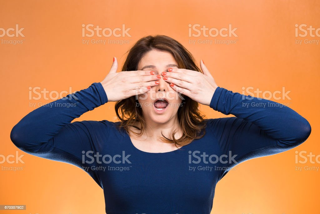 young, coy woman, female closing eyes with hands can't see, hiding, mouth open stock photo