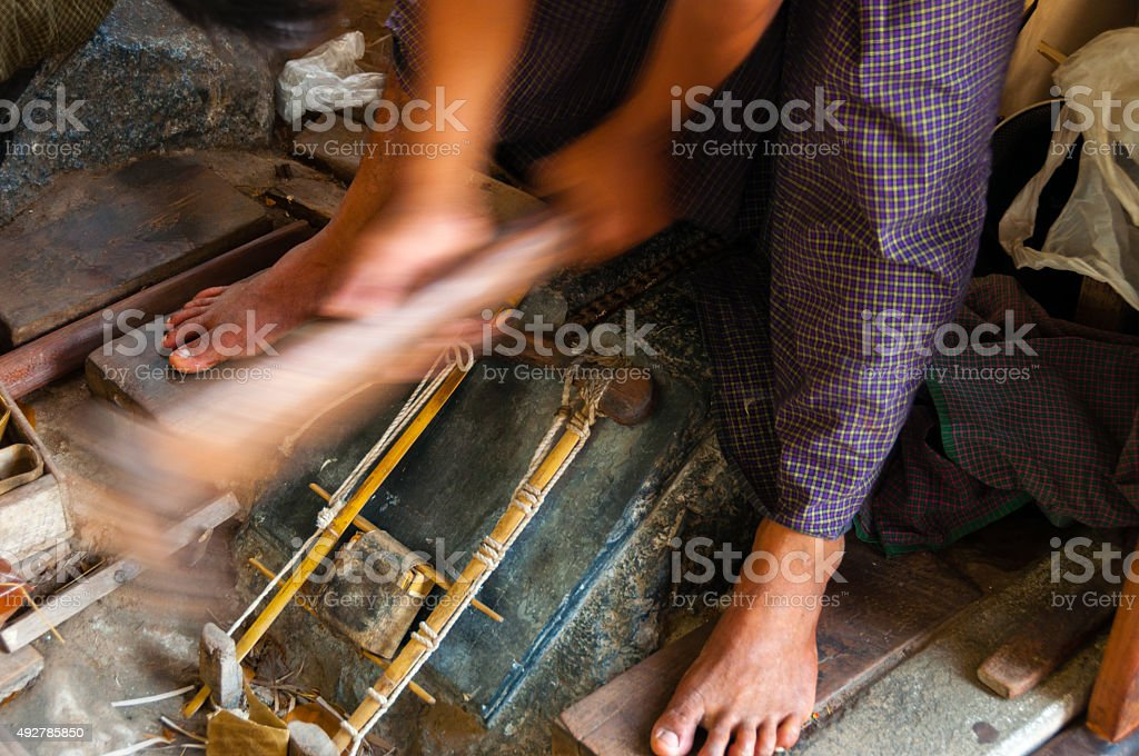 Young craftsman punching gold with a hammer stock photo