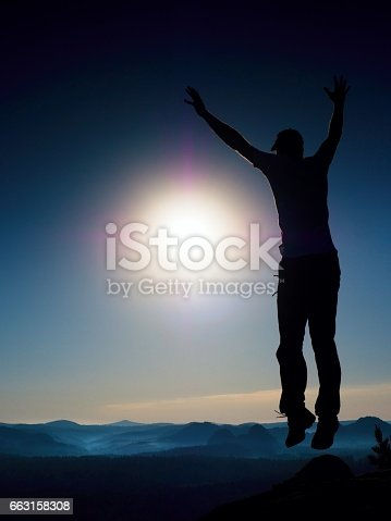 istock Young crazy man is jumping on colorful sky background 663158308