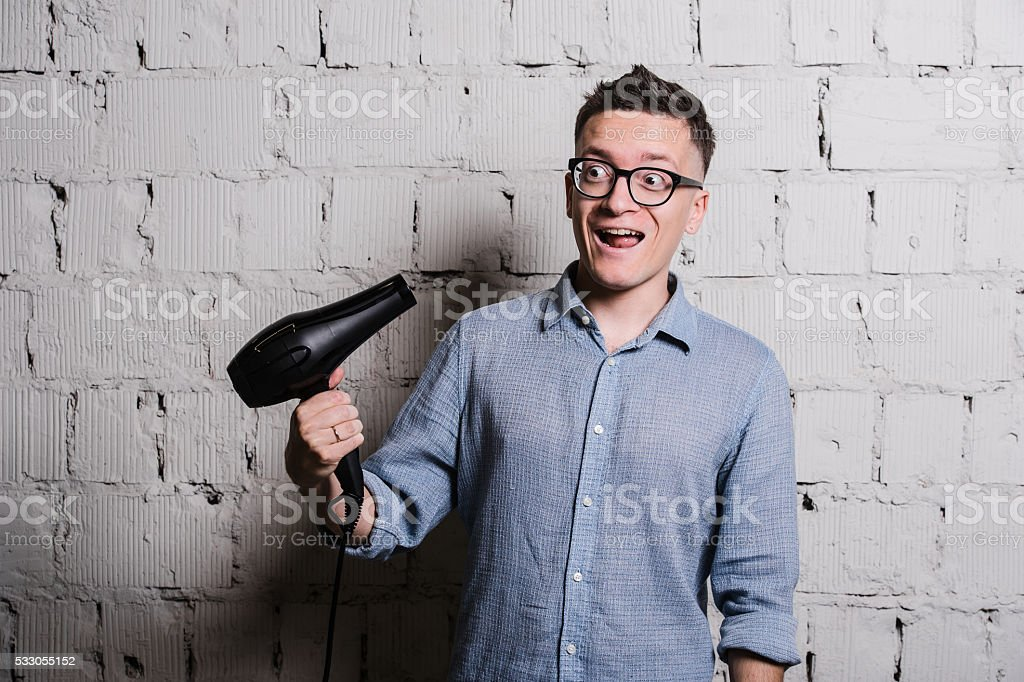 Young crazy stylish man with hairdraier and funny expressions on stock photo