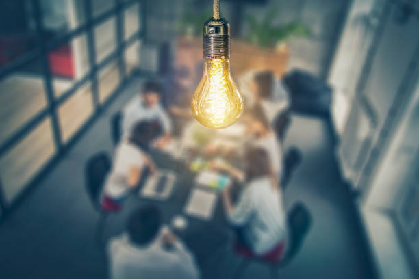 Young creative business people meeting at office. Young business people are discussing together a new startup project. A glowing light bulb as a new idea. collaboration stock pictures, royalty-free photos & images