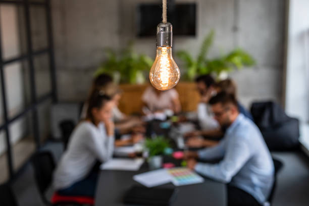 Young creative business people meeting at office. Young business people are discussing together a new startup project. A glowing light bulb as a new idea. market research stock pictures, royalty-free photos & images