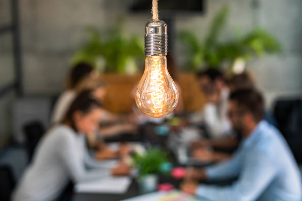 Young creative business people meeting at office. Young business people are discussing together a new startup project. A glowing light bulb as a new idea. customer engagement stock pictures, royalty-free photos & images