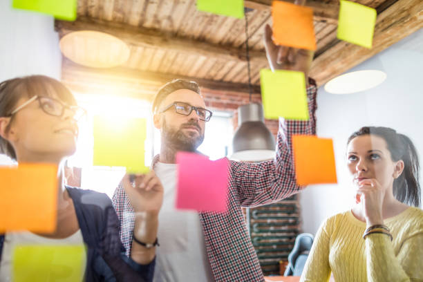 Young creative business people meeting at office. Business people meeting at office and use post it notes to share idea. Brainstorming concept. Sticky note on glass wall. market research stock pictures, royalty-free photos & images