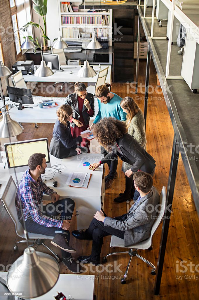 Young creative business people talking in office stock photo