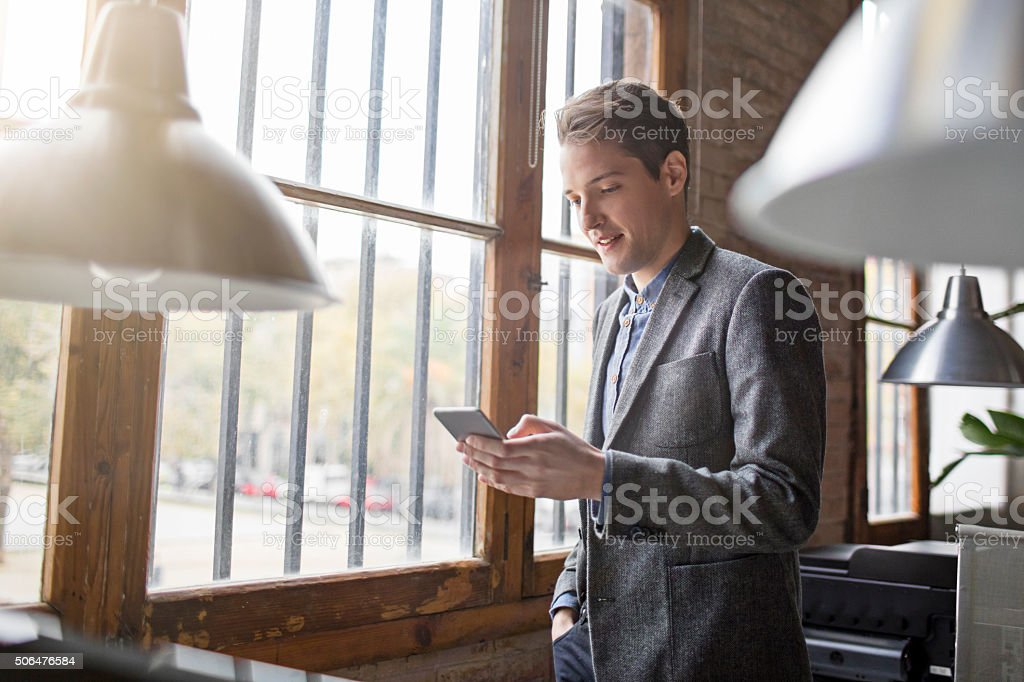 Young creative businessman at the window looking on mobile phone stock photo