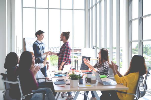 joven creativo diseño asiático feliz cálida bienvenida al nuevo cowork empleado en la reunión o formación en la oficina. feliz lugar de trabajo asiático en pequeñas empresas o startup en concepto de millennials con tono suave. - oficina de empleo fotografías e imágenes de stock