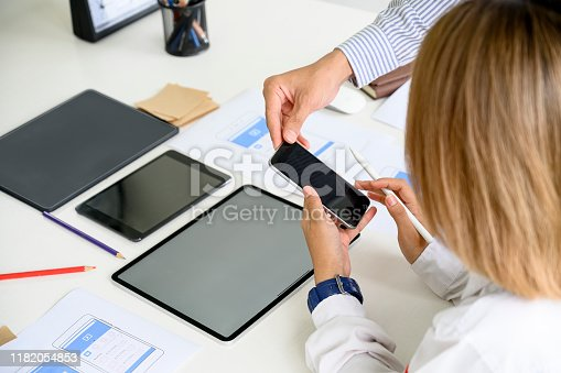 995213208 istock photo Young creative disigner team working together at office, using smartphone and tablet for new project. 1182054853