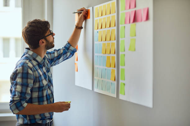 young creative man writing down ideas on wall full of sticky notes - post it notes стоковые фото и изображения