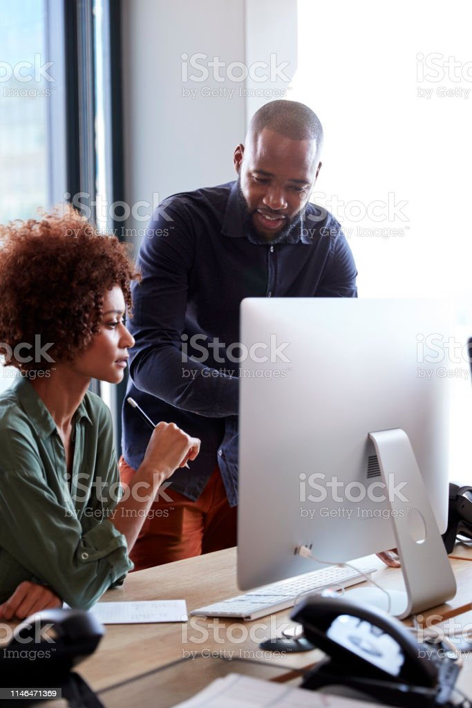 Young creative professionals working together at a computer in an...