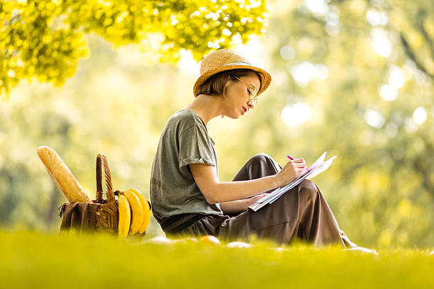 Young creative woman sketching on the paper at picnic. ストックフォト