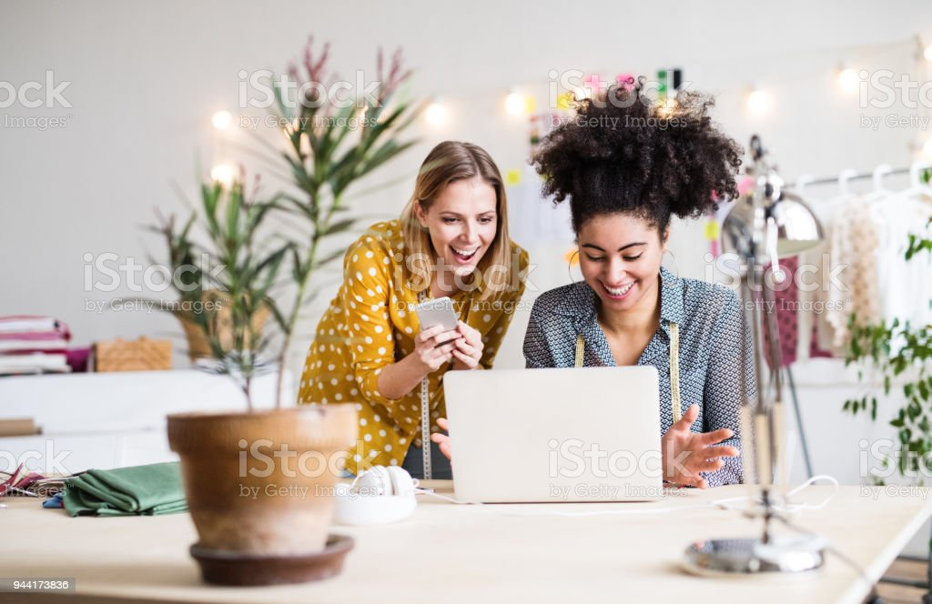 Young creative women with laptop in studio, startup business. stock photo