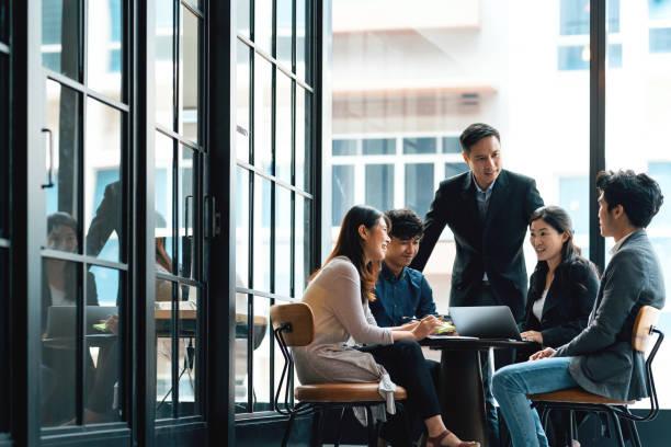在開放的工作環境中進行討論的年輕創意者和團隊領導者 - 亞洲 個照片及圖片檔
