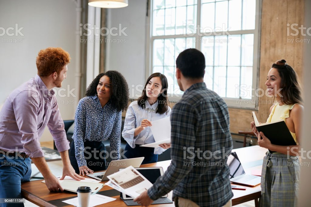 Young creatives brainstorming ideas around a table stock photo