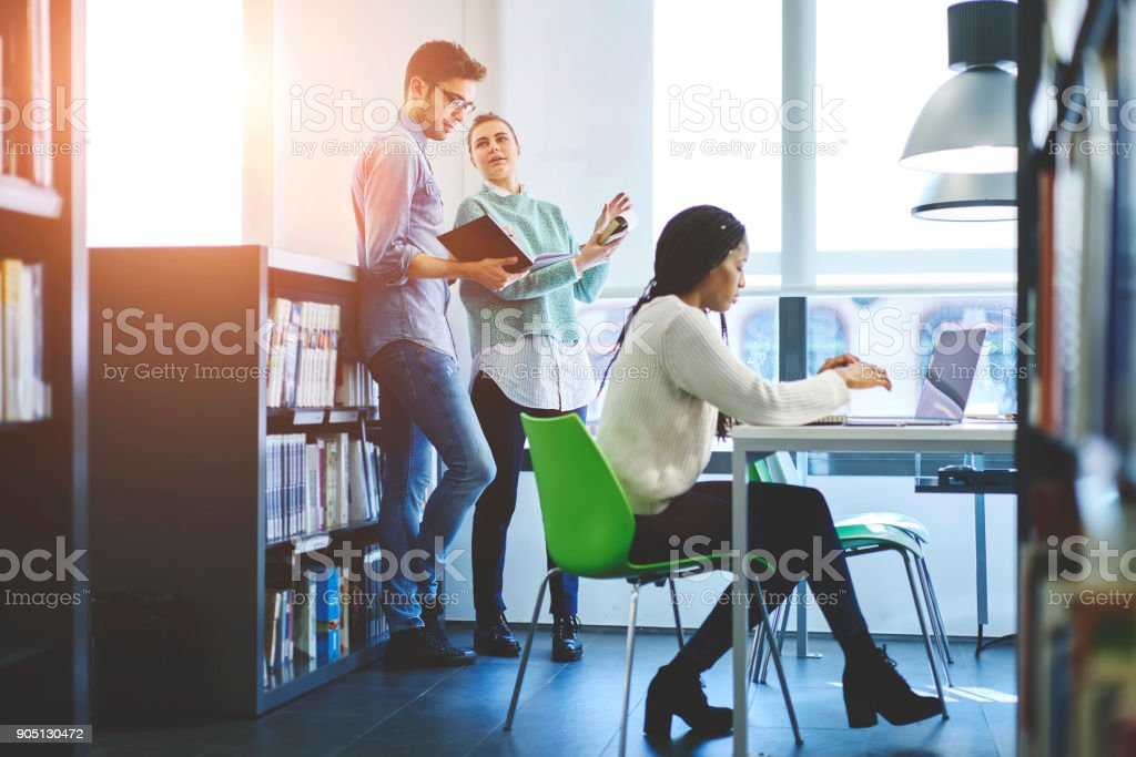 Young crew of male and female coworkers cooperating researching and analyzing information for business startup, international student preparing for examination together  in university library stock photo
