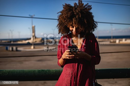 946192604 istock photo Young Cuban woman hanging mobile 1253251070