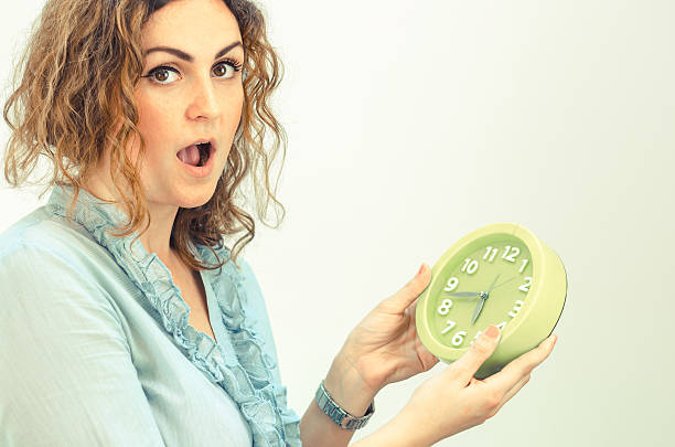 young curly girl holding a clock - omg stock photos and pictures