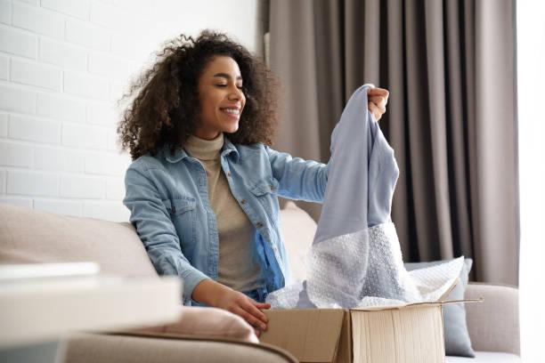 junge lockige haare zufrieden eafrikanische mädchen dame shopaholic kunden sitzen auf sofa auspacken paket lieferbox blick auf kleidung nehmen grauen pullover pullover, online-shopping versandkonzept. - bekommen stock-fotos und bilder