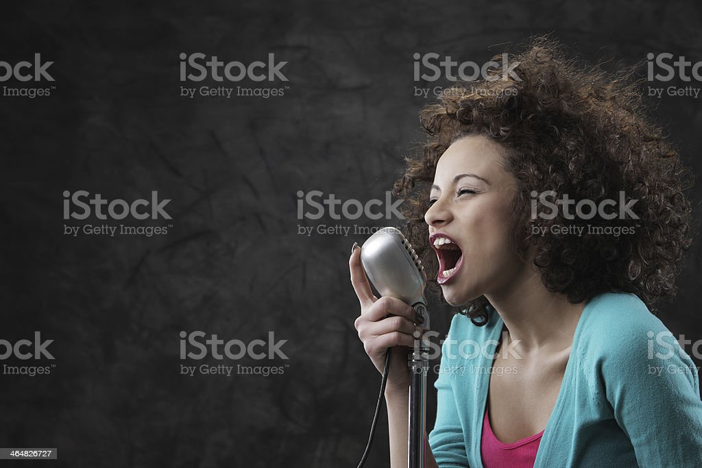 Young curly haired woman yelling into old school microphone stock photo