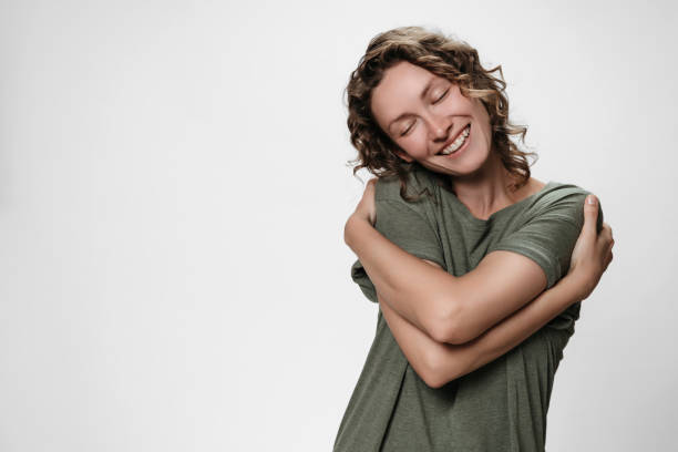 Young curly woman hugging herself, looks happy, expresses natural positive emotions Young curly woman hugging herself, looks happy, loves herself, has high self esteem, smiles from pleasure. Isolated over white, free copy space for your text. Self love and self care concept. low self esteem stock pictures, royalty-free photos & images