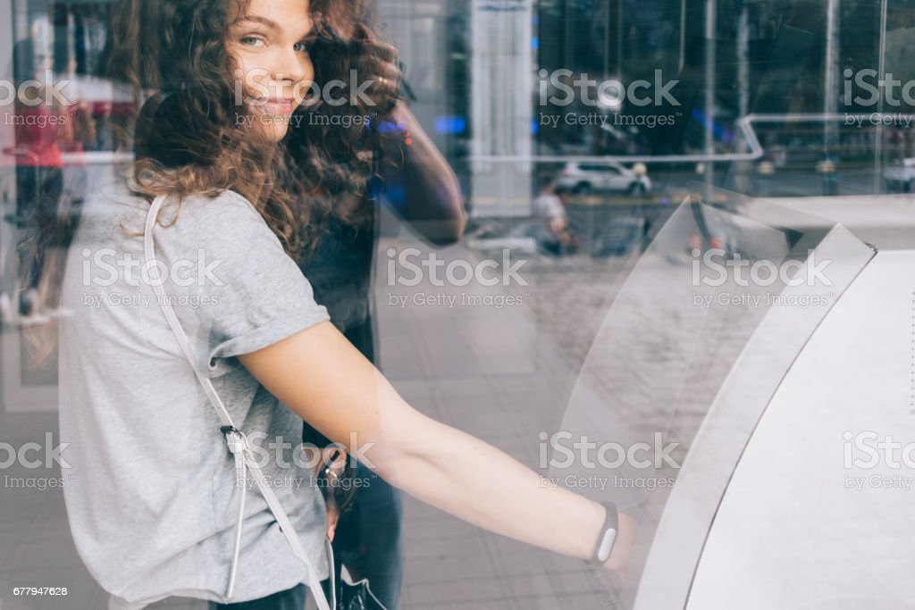 Young curly-haired smiling woman withdraws money from an ATM in the city stock photo