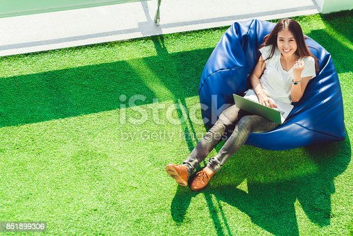 istock Young cute Asian girl celebrate with notebook laptop, sit on bean bag in garden, copy space on green grass. Success small business, modern lifestyle, information technology, or online shopping concept 851899306