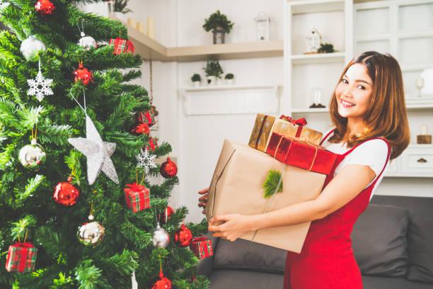 junge süße asiatin holding x'mas präsentieren boxen, geschmückter weihnachtsbaum mit schmuck zu hause wohnzimmer. xmas feier event vorbereitung oder winter urlaub indoor festivalparty konzept - weihnachten japan stock-fotos und bilder