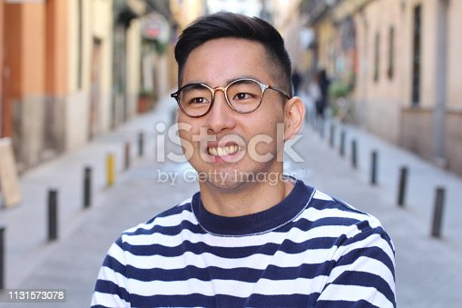 Young cute Asian man smiling outdoors.