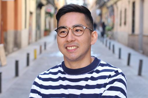 Young cute Asian man smiling outdoors.